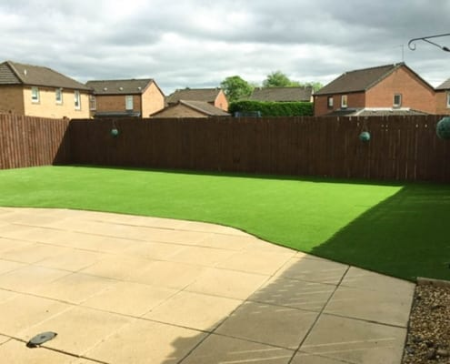 Artificial Lawn Installation Summerston Glasgow - an artificial lawn and patio in a garden on a sunny day.