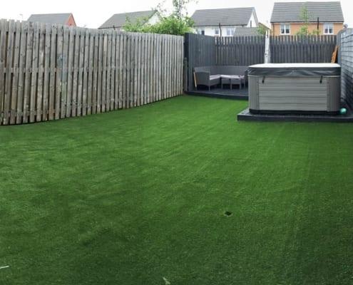 Artificial Lawn Installation Ravenscraig, a beautiful lush green artificial lawn in a back garden.